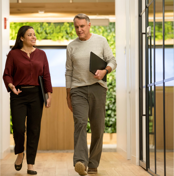 Two professional colleagues talking as they walk through an office.