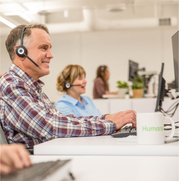 A smiling man in a call center talking on a headset.