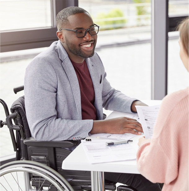 A young professional sitting in a wheelchair at his desk.