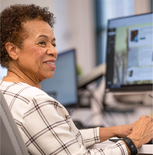 An older professional woman sitting at a desk looks back and smiles.