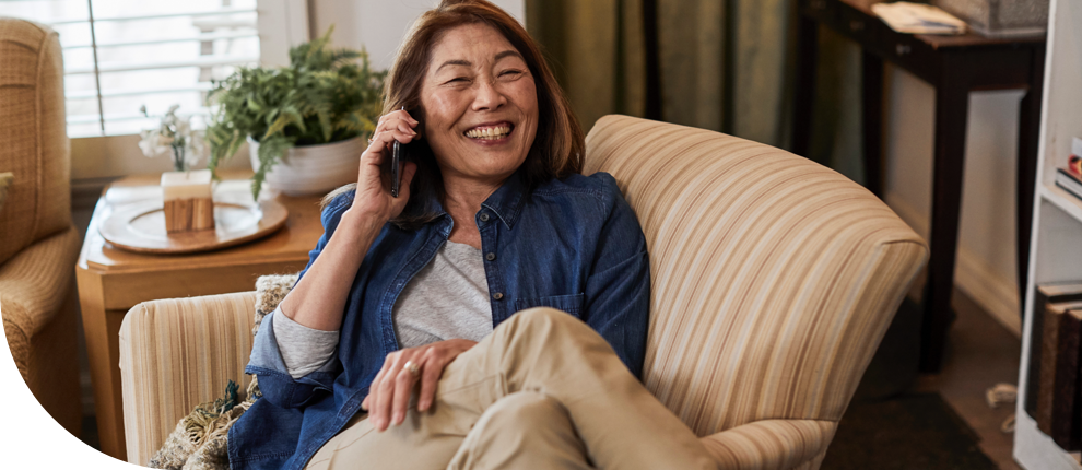 A smiling woman sitting in an armchair and talking on the phone.