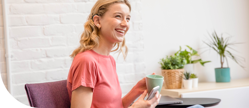A smiling student sitting at an office desk with a cup of coffee.