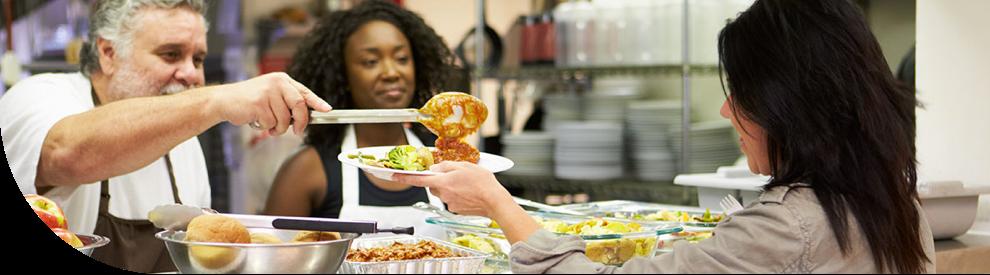 A man serving a woman at a soup kitchen.