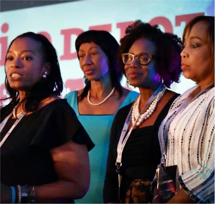 four black women standing on a stage together