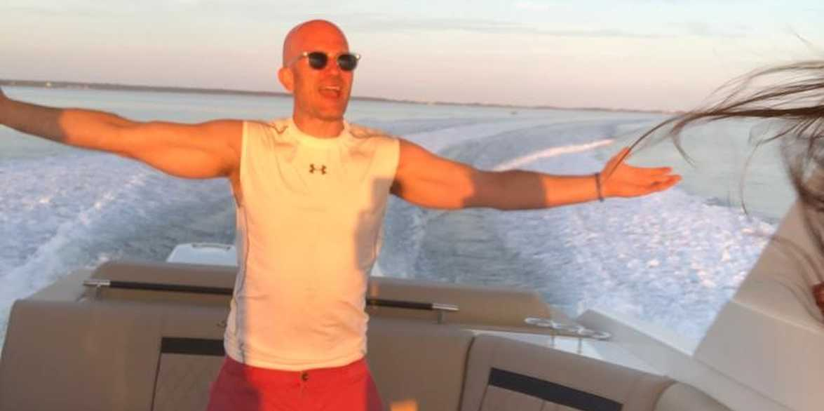 Jeff standing at the back of a boat with arms spread wide