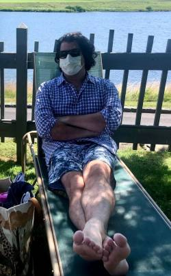 Cary Feurer, masked up, reclining on a lounge chair