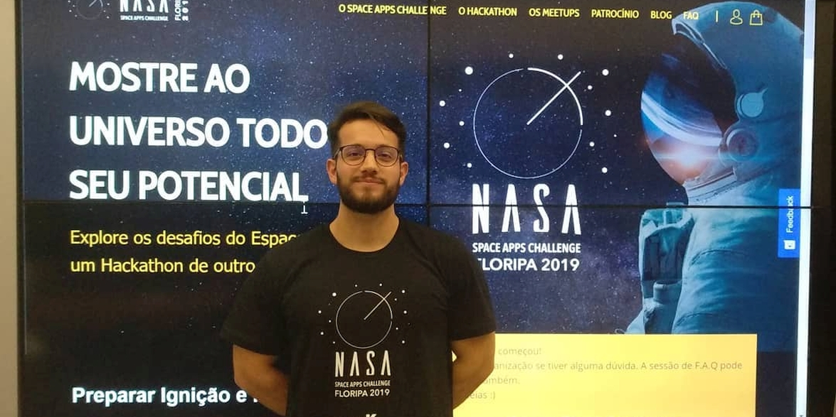 Carlos standing in front of NASA sign