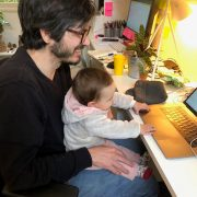 Roberto and his baby daughter seated at a desk with a laptop.
