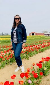 Tashina stands in field of tulips