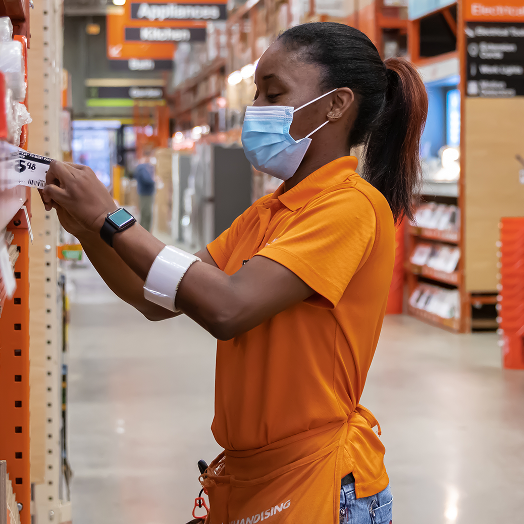 Woman working in a Home Depot store while wearing a mask