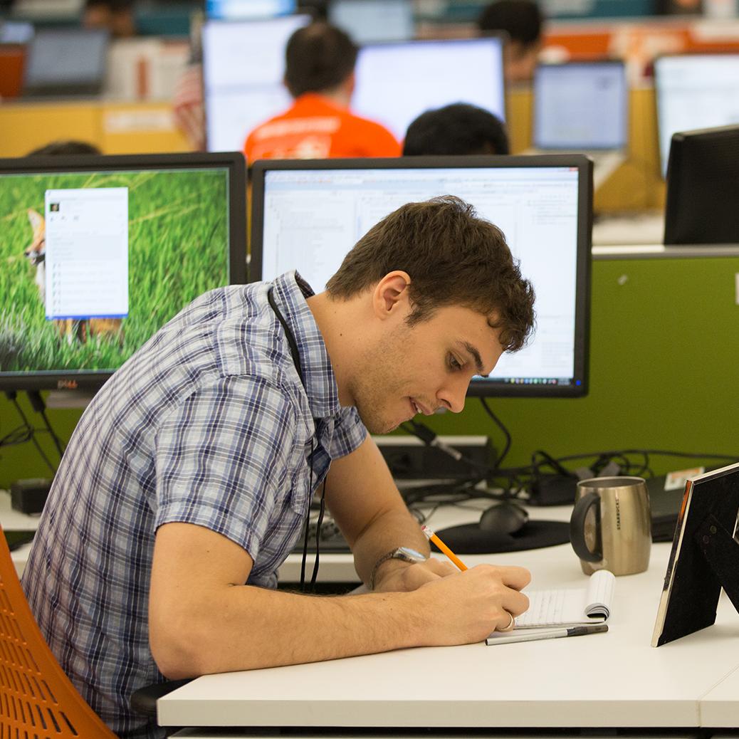Man sitting at a cubicle, writing