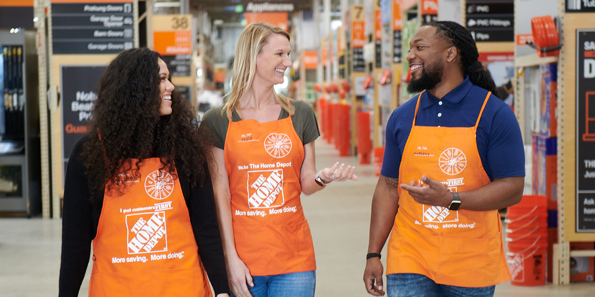 Three Home Depot employees walking through a store aisle while talking and smiling