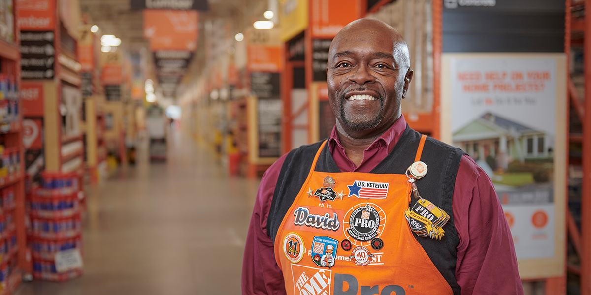 Man posing for photo in an aisle, wearing his Home Depot apron adorned with pins