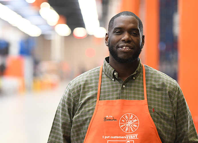 Man in Home Depot apron looking at camera and smiling