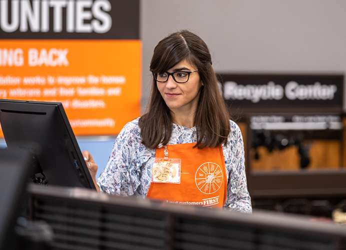 Home Depot store employee, cashier, entering data on a touchscreen