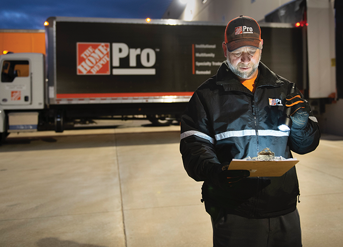 Home Depot driver reviewing his manifest on a clipboard in front of a Home Depot Pro truck