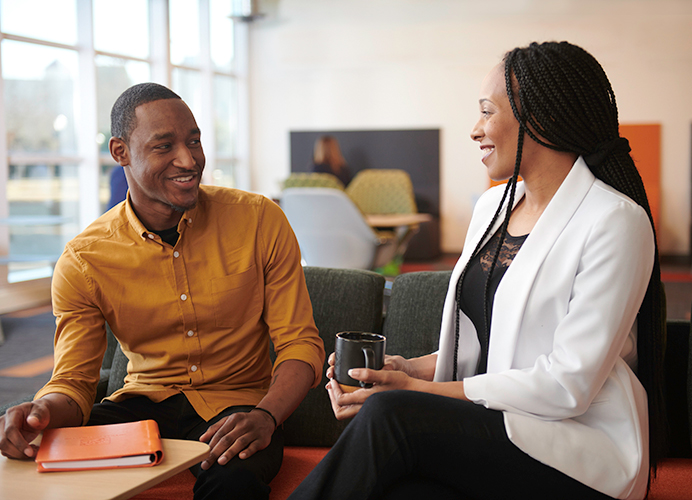 Man and woman at a corporate office, smiling at one another