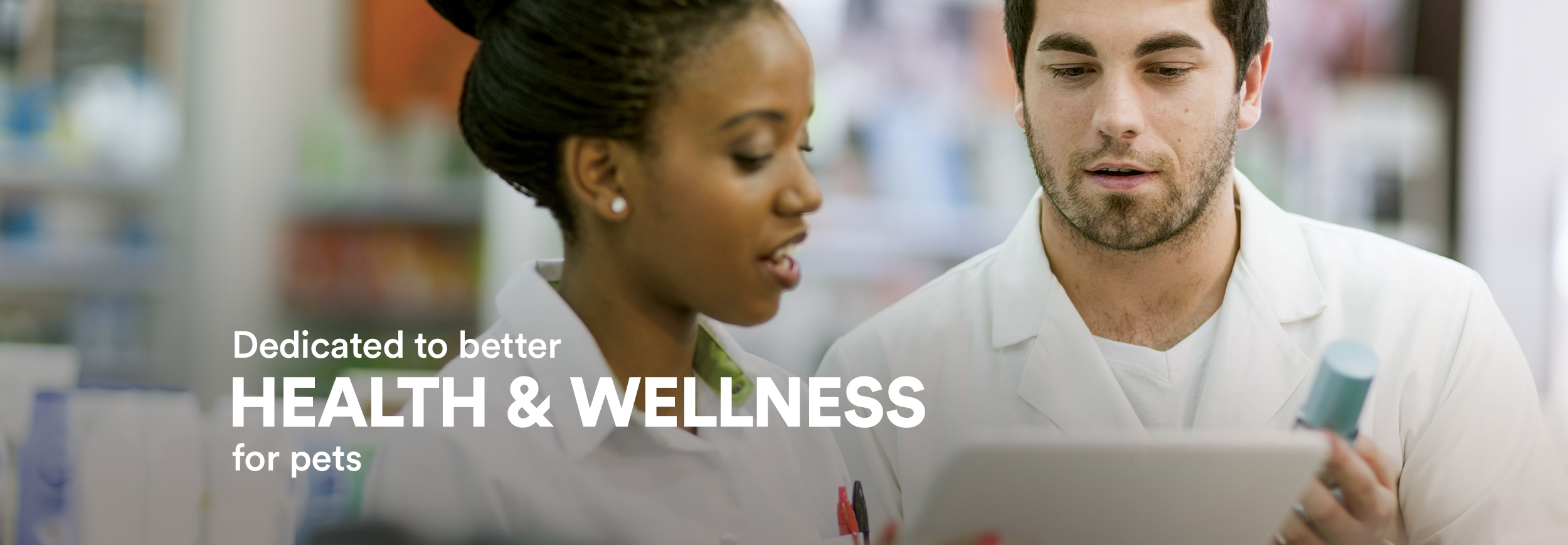 "A male and a female Pharmacist confer over a clipboard and medications to find the correct prescription. Text across the image reads, ""delivering solutions for healthier, happier pets."""