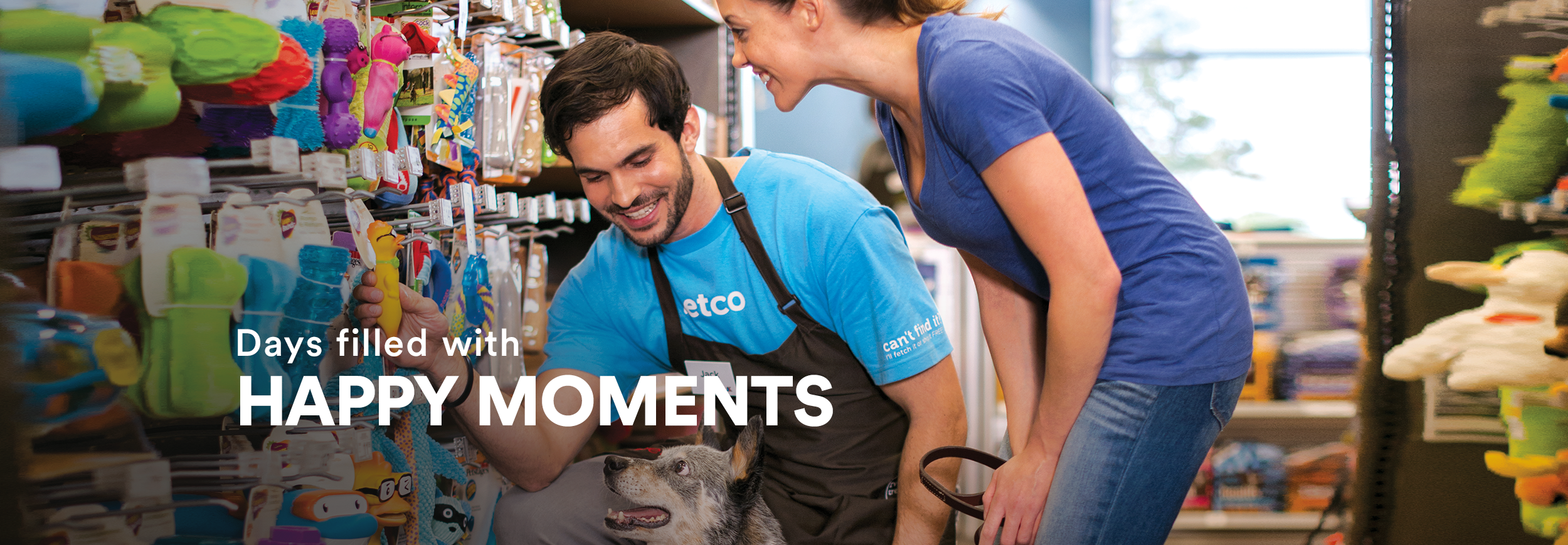 """Male store employee showing a dog and his owner a new toy on the wall. The dog's expression is very excited. Text across the image reads, """"happy hour now lasts your whole shift."""""""