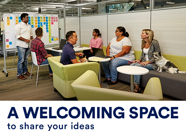 """A gathering of diverse men and women meeting in an informal lounge, with a whiteboard covered in sticky notes in the background. In the foreground, a little dog sits on the sofa beside his female owner. Text across the image reads, """"team meetings come with wags included."""""""