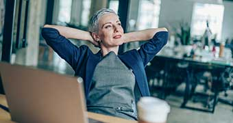 Women leaning back in office chair smiling