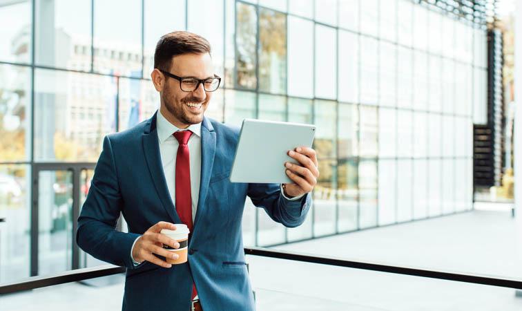 Smiling modern businessman using tablet on coffee break