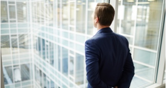 A man looks out the window of a high-rise office building