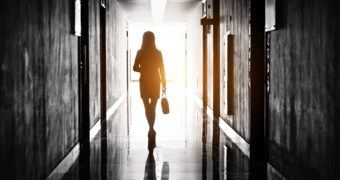 Silhouette of a woman walking down a corridor