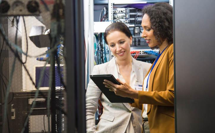 Women in data center programing mainframe through digital tablet.