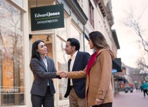 Une représentante en services financiers Edward Jones serre la main d'une cliente à l'extérieur d'un bureau pendant qu'un client les regarde.