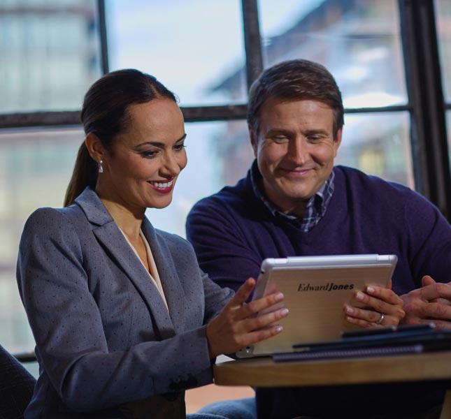 Un homme regarde une tablette que tient une représentante en services financiers.