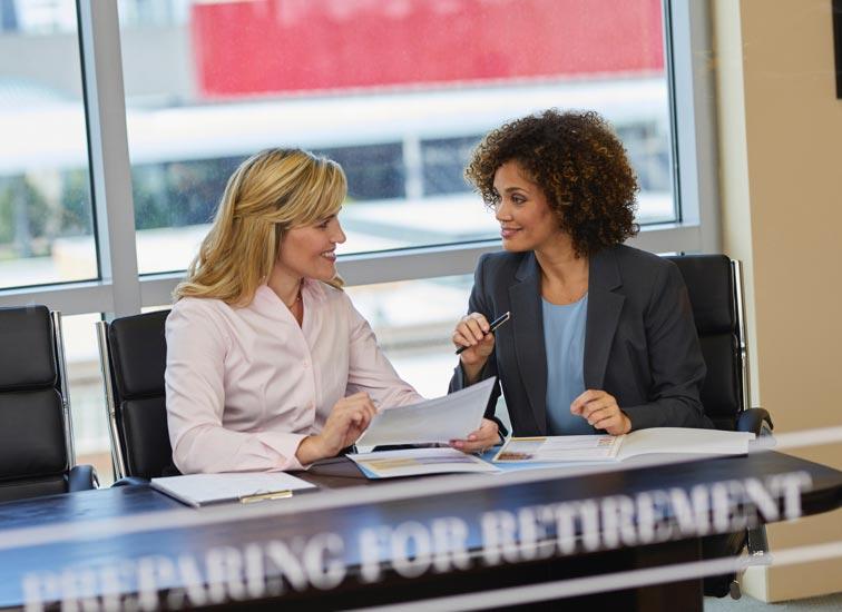 Deux femmes discutent, assises à une table.
