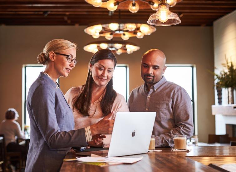 Une représentante en services financiers pointe l'écran de son ordinateur portable en discutant avec une femme et un homme.