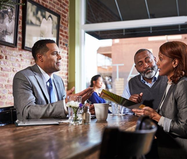 Un représentant en services financiers assis à une table de restaurant parle à un couple.