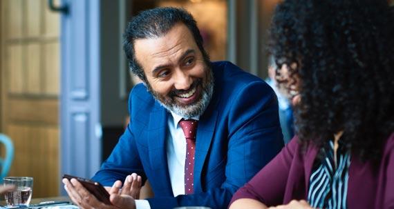 Un homme et une femme assis à une table regardent un téléphone mobile.