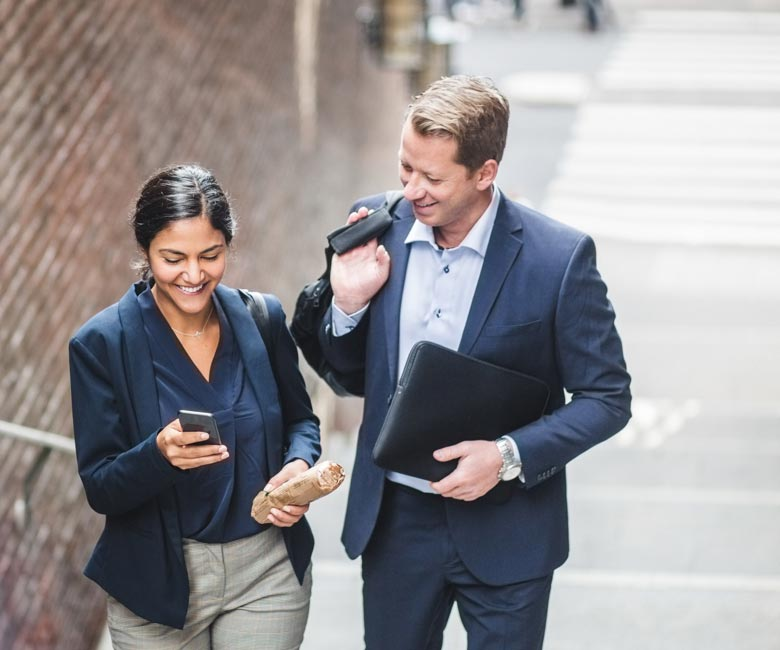 Un homme et une femme regardent un téléphone cellulaire pendant qu'ils montent un escalier.