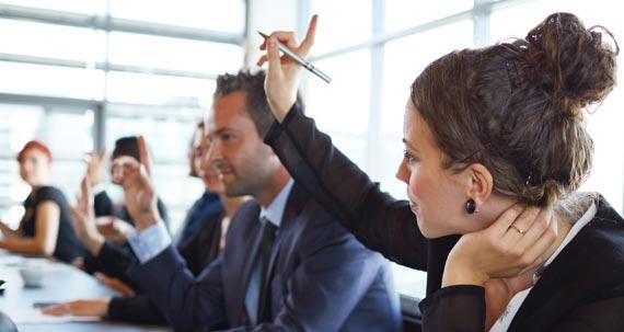 Un groupe d'adultes sont dans une salle de conférence. Une femme lève la main.