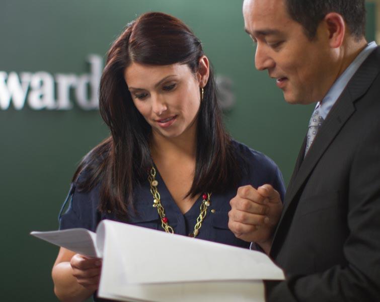 Un représentant en services financiers et un client examinent des documents.