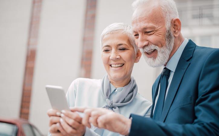 Un couple âgé regarde un téléphone cellulaire.