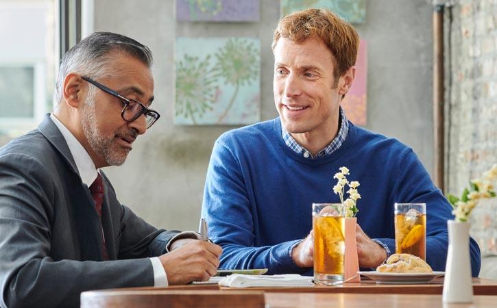 Deux hommes animent une réunion à une table en mangeant.