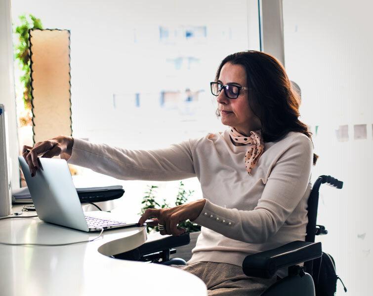 Une femme ouvre son ordinateur portable.