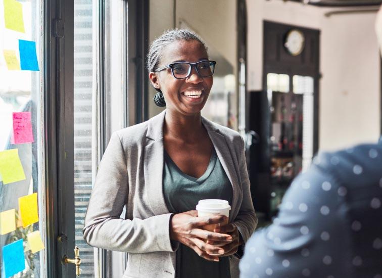 Une femme, debout près d'une fenêtre lumineuse, tient une boisson pendant qu'elle discute avec une autre personne.
