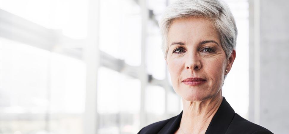 Une femme d'affaires aux cheveux blancs est debout près de fenêtres de bureaux lumineuses.