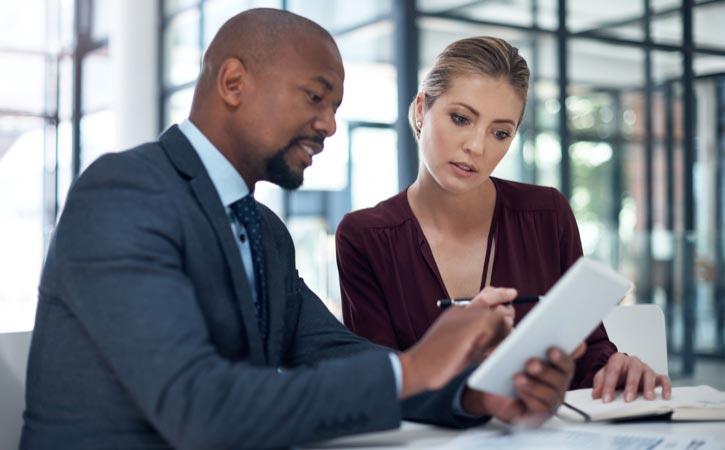 Un homme et une femme d'affaires regardent une tablette numérique dans un bureau d'allure moderne.