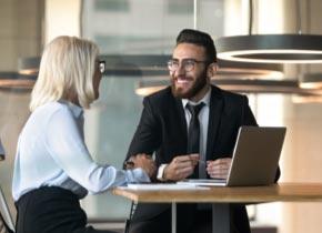 Un homme et une femme assis à une table parlent et regardent un ordinateur portable.