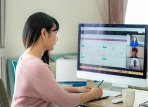 Une femme devant un écran d'ordinateur rédige une note.