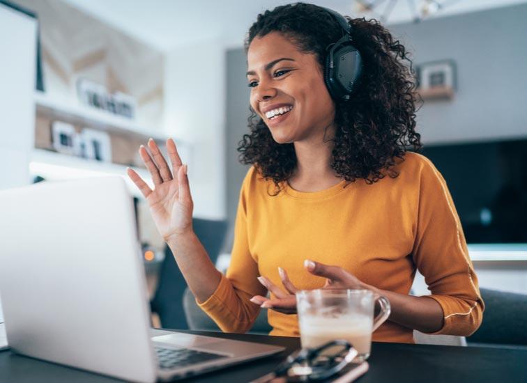 Une femme portant un casque d'écoute parle à d'autres personnes sur son ordinateur portable.
