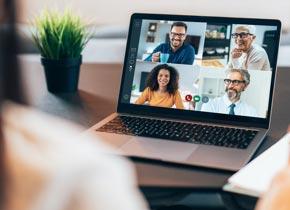 Une personne regarde une réunion en ligne sur un écran d'ordinateur portable.
