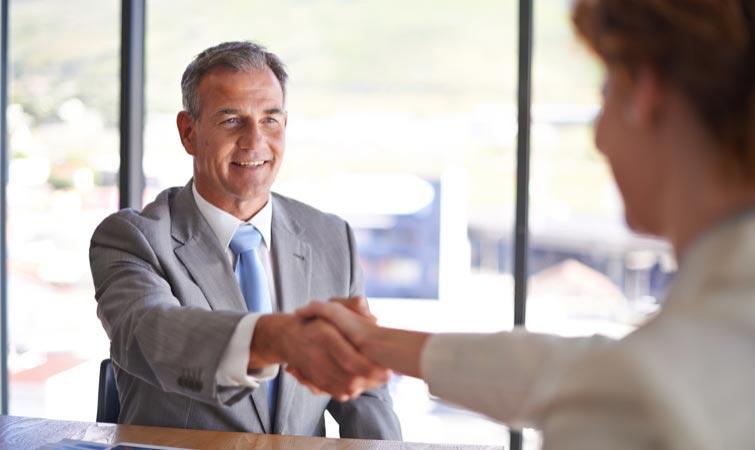 Un homme d'affaires qui serre la main d'un collègue dans une salle de conférence.