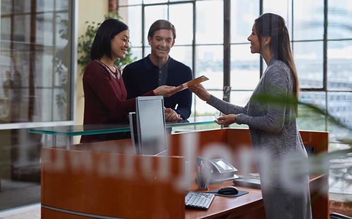 Un couple remet des papiers à une femme debout derrière un bureau.